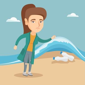 Женщина показывая пластичные бутылки под морской водой.
