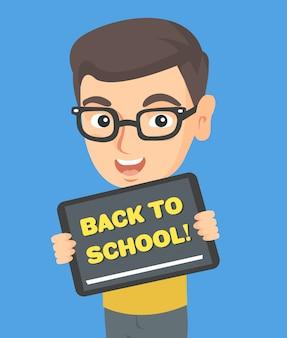 学校に戻ってテキストとタブレットを保持している少年。