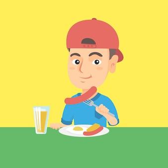 朝食にソーセージと目玉焼きを食べる少年。