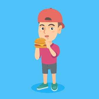 Маленький кавказский мальчик ест гамбургер.