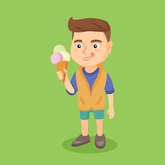 Маленький кавказский мальчик держа конус мороженого.