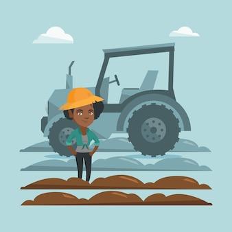 トラクターの隣に立っている農夫。