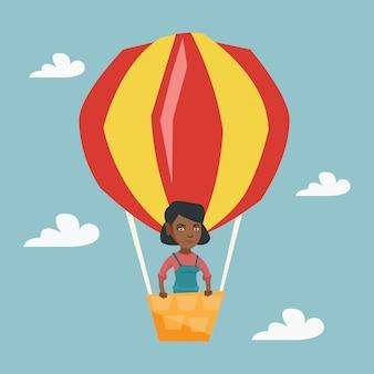 熱気球で飛んでいる若いアフリカ人女性。