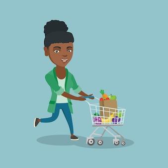 ショッピングカートで走っているアフリカの女性。