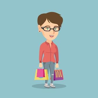 買い物袋を持つ若い幸せな白人女性。