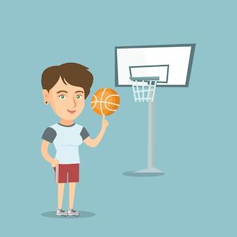 若い白人のバスケットボール選手がボールを回します。
