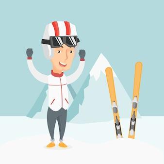 上げられた手で立っている陽気なスキーヤー。