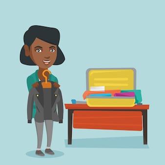 アフリカの女性がスーツケースに服を梱包します。