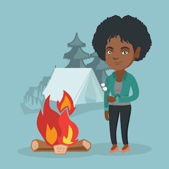 キャンプファイヤーでマシュマロを焙煎するアフリカの女性。