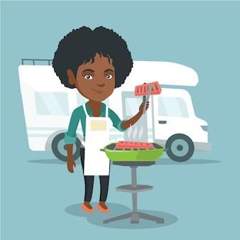 キャンピングカーの前で肉を焼く女性。