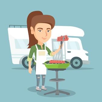 Женщина готовит мясо перед автофургоном.