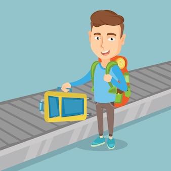 男は荷物コンベアベルトにスーツケースを取ります。