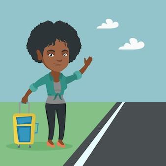ヒッチハイクのスーツケースを持つ若いアフリカ人女性。
