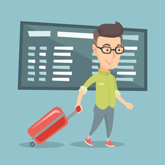 空港でスーツケースを持って歩く男。