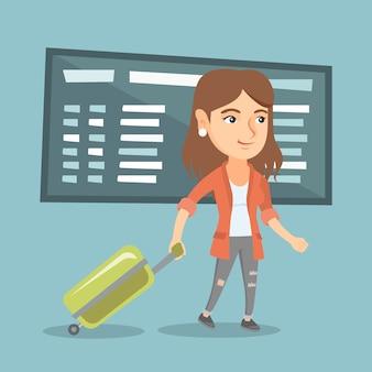 空港でスーツケースを持って歩く白人女性。