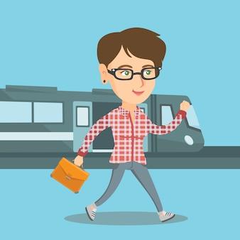 鉄道駅プラットフォームの上を歩く若い女性。
