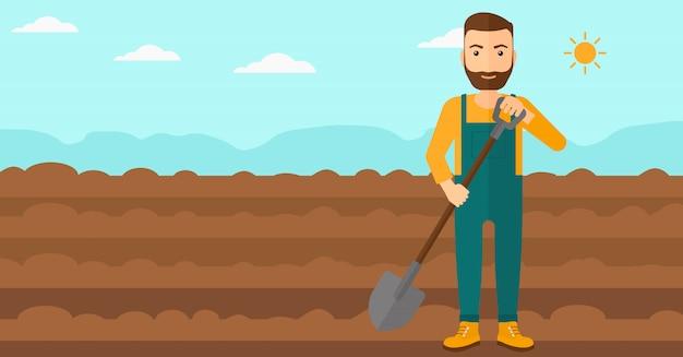 Колхозник на поле с лопатой.