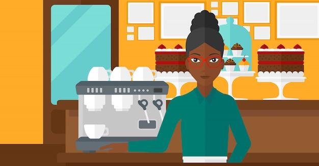 Бариста стоит возле кофеварки.