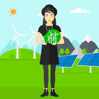 Женщина, держащая лампочку с ветряными мельницами внутри