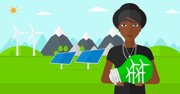 内部の風車と電球を保持している女性