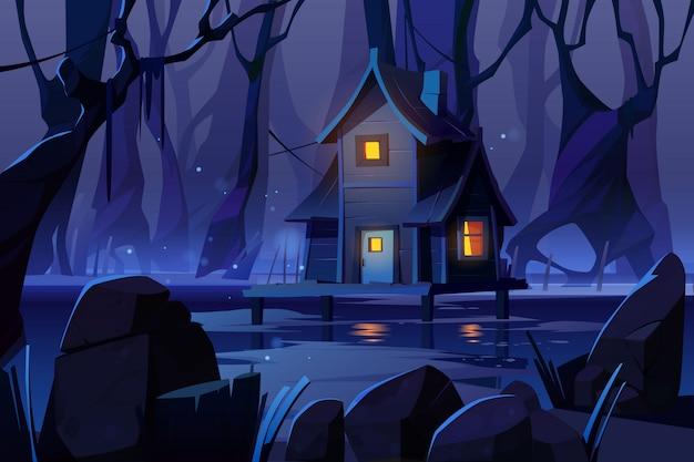 夜の森の沼に木製の神秘的な高床式の家