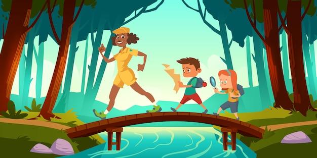 ハイカーは森の川を渡る橋を渡って歩く