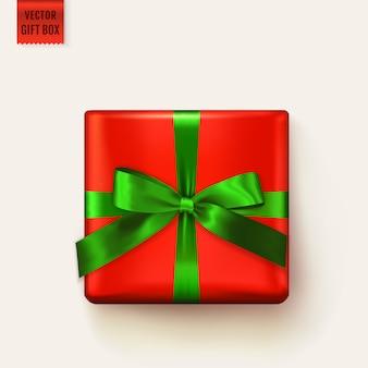リボンで結ばれたギフトボックス。クリスマスデザイン、誕生日グリーティングカード、販売バナーまたはその他の装飾のための現実的な分離要素。緑の弓と赤の広場ギフトボックス。上面図。
