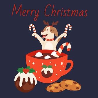 チョコレート、冬の休日のケーキとキャンディーのイラストのマグカップとクリスマスのトナカイの角でかわいい犬。メリークリスマスカード。
