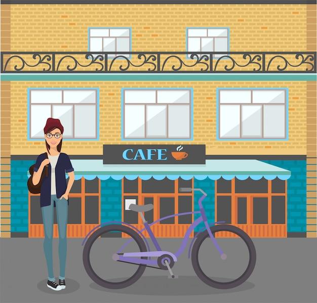 Молодая усмехаясь женщина с иллюстрацией велосипеда. счастливая милая девушка стоя около велосипеда перед зданием кафа города. городская езда модные велосипедные перевозки.