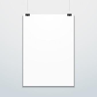 Вертикальный плакат подвешен на макете офисных клипов