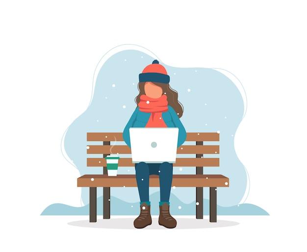 冬のコーヒーとベンチにコンピューターを持つ少女。