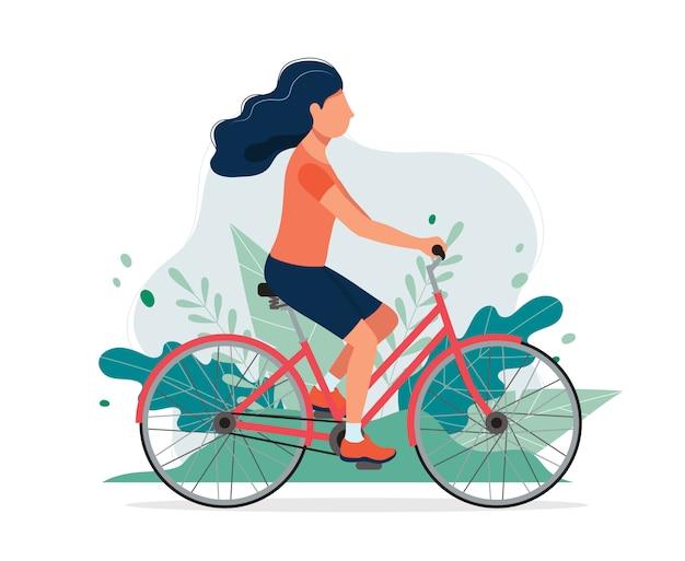 公園で自転車で幸せな女。