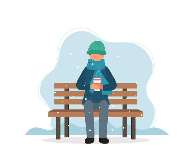 Человек сидит на скамейке зимой с кофе.