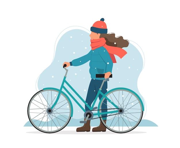 Девушка с велосипедом в парке в зиме.