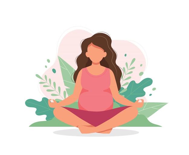 Беременная женщина занимается йогой с листьями