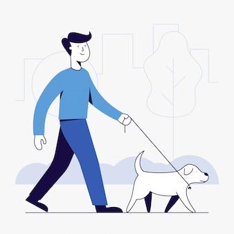 若い男と公園を散歩している犬。