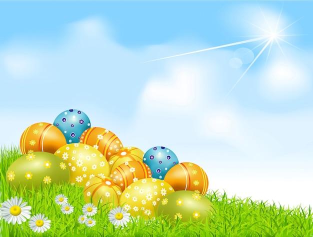 Пасхальные яйца на зеленом поле с ромашками и голубым небом