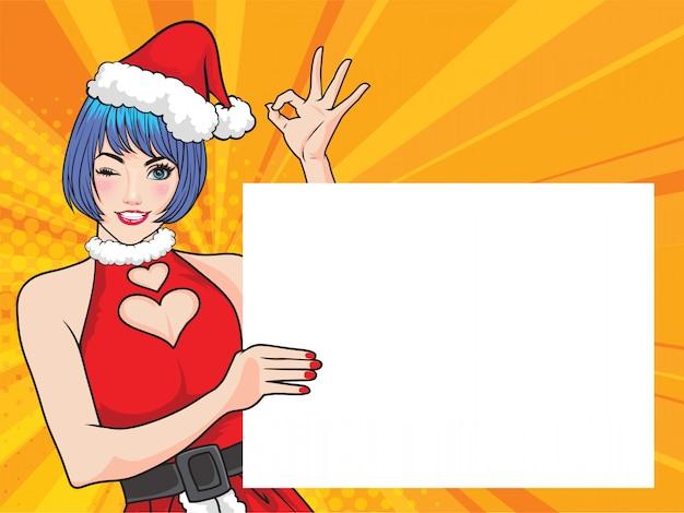 Милая женщина санты показывая пустой плакат и вручает одобренное действие