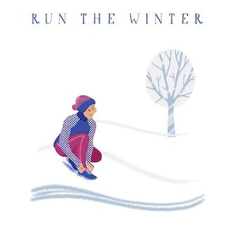 Женщина в теплой зимней одежде завязывает шнурки в заснеженном парке