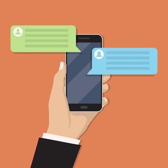 チャットメッセージを持つスマートフォンを持っている手
