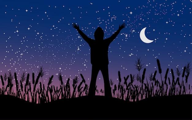 月と空の星がいっぱい草で一人で立っている男