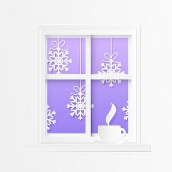 雪とお茶のカップを持つ冬のウィンドウ。