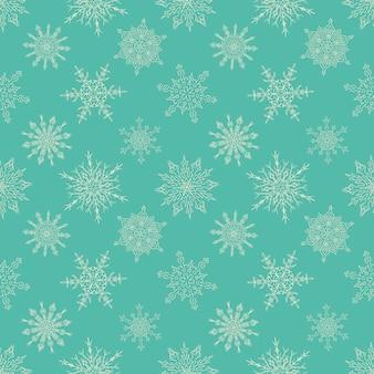 描かれた雪の結晶のシームレスなクリスマスグリーンパターン