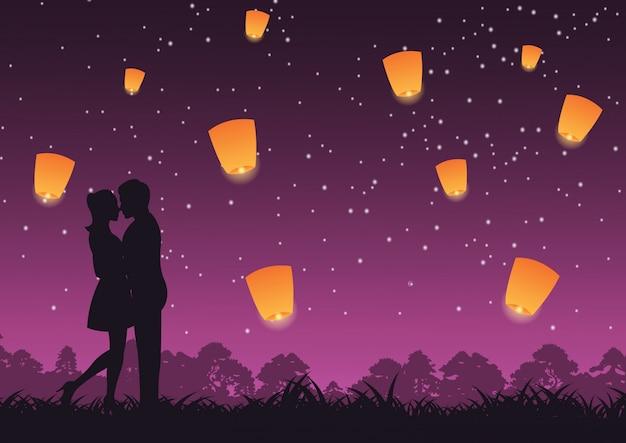 カップルが一緒に抱擁し、上記のランタンをキスします。