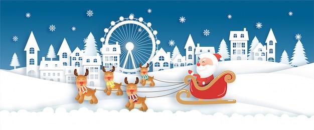 サンタとクリスマスカードの雪の村でかわいいトナカイとのクリスマスのお祝い
