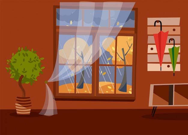 黄色の木と葉の景色を望む窓。ハンガーに傘を持つ秋の茶色のインテリア。外の雨の夜。