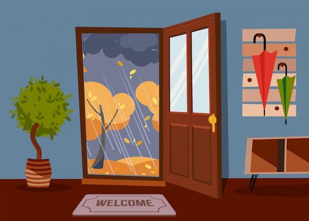開いたドア、傘が付いているコートラックが付いている内部の廊下の壁。秋の雨の夜と黄色の木の外。