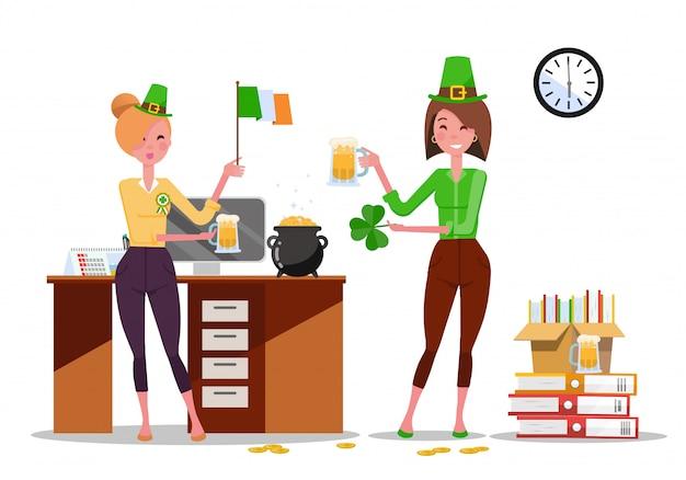 Две молодые женщины-служащие празднуют день святого патрика на рабочем месте с пивными кружками и флагом ирландии в руках