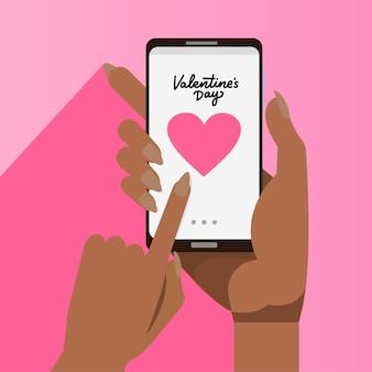 画面に大きな心でスマートフォンを保持しているアフリカの女性の手。