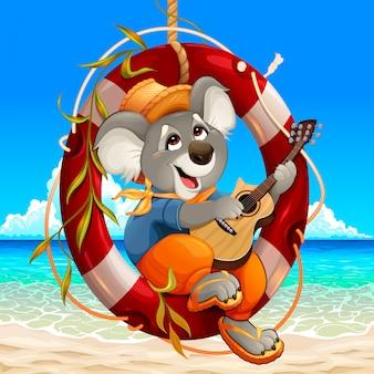 コアラはビーチでギターを弾いています